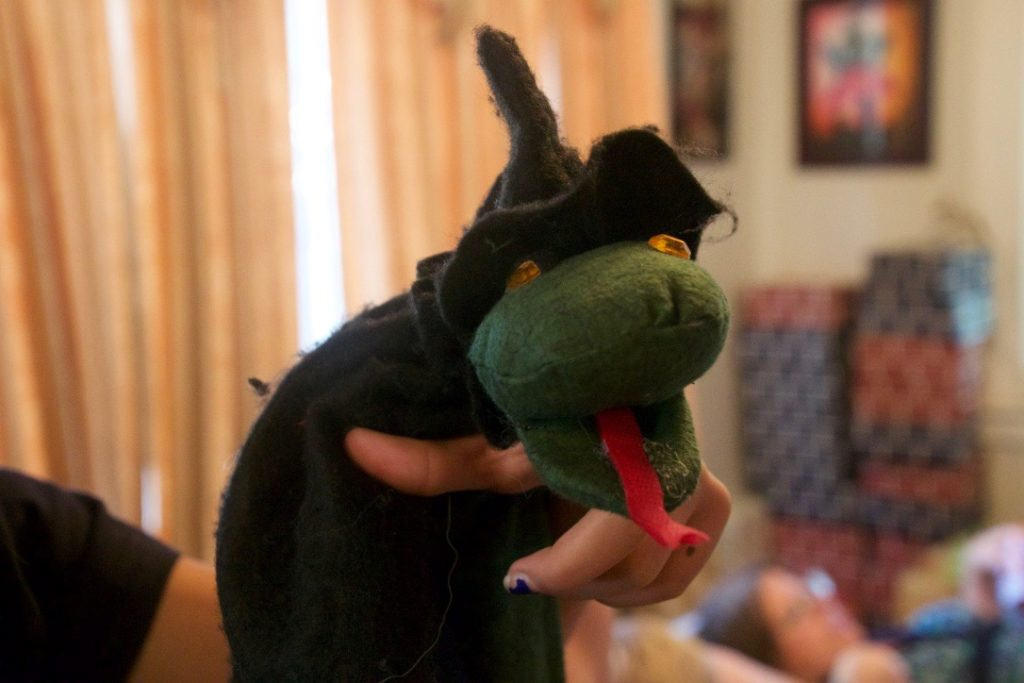 Penelope Torribio taught student to sew costumes and puppets-first with a sample snake puppet.